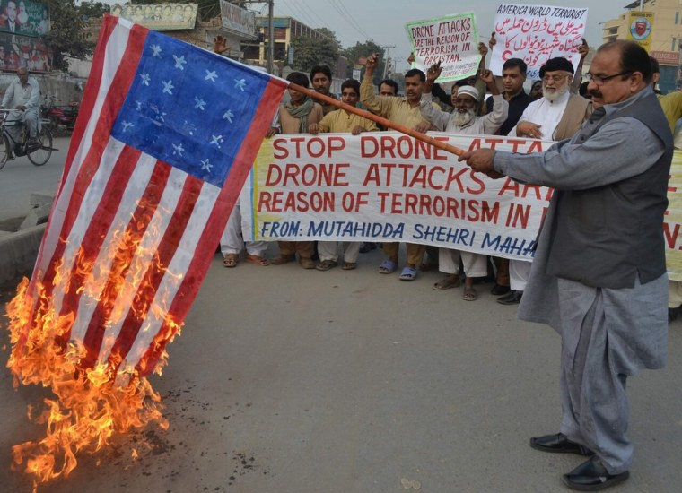 A demonstrator holds up a burning US flag during a protest against drone attacks in Pakistan's tribal region, in Multan on December 6, 2012. (S.S MIRZA/AFP/Getty Images)