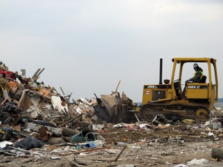 A worker uses a bulldozer to push debris from Superstorm Sandy into a large pile in Lavallette N.J.  Friday, Jan. 4, 2012, shortly before Congress voted to approve aid for storm victims. (Photo by Wayne Parry/AP Photo)