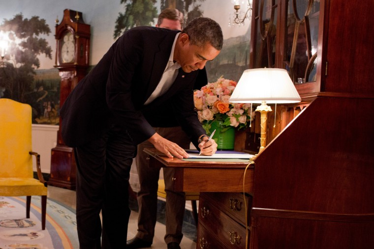 President Barack Obama, signs H.R. 41, which temporarily increases the Federal Emergency Management Agency's borrowing authority for carrying out the National Flood Insurance Program, in the Diplomatic Reception Room of the White House Jan. 6, 2013. ...