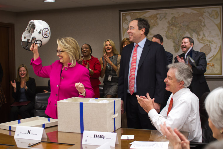 Secretary of State Hillary Clinton receives a football helmet imprinted with the State Department logo from her staff on January 7, 2013. (Photo by Nick Merrill/Department of State)