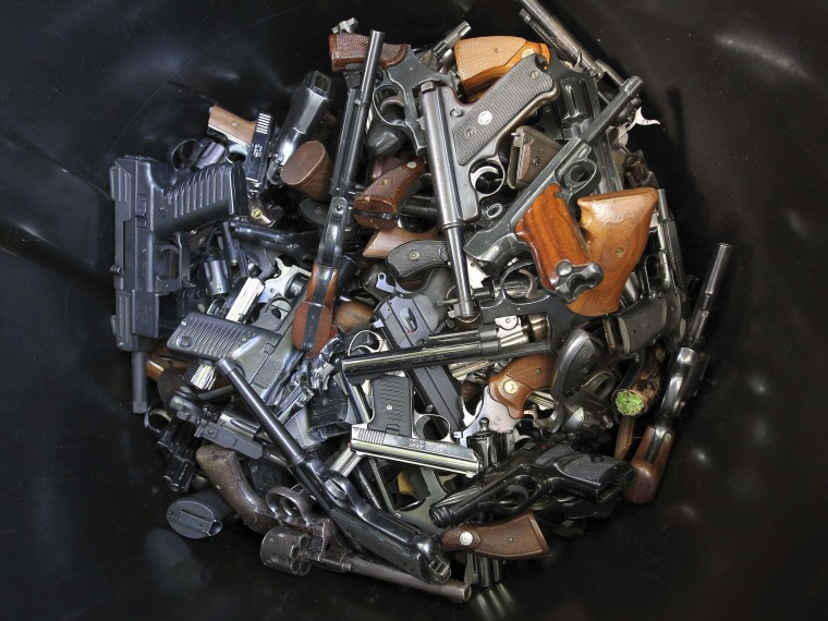 Hand guns that were turned in by their owners are seen in a trash bin at a gun buyback held by the Los Angeles Police Department following the mass shooting at Sandy Hook Elementary School in Connecticut, in Los Angeles, California, December 26, 2012. ...