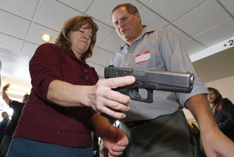 A Utah teacher is shown how to handle a handgun by instructor Clint Simon (R), at a concealed-weapons training class to 200 Utah teachers on December 27, 2012 in West Valley City, Utah. The Utah Shooting Sports Council said it would waive its $50 fee...