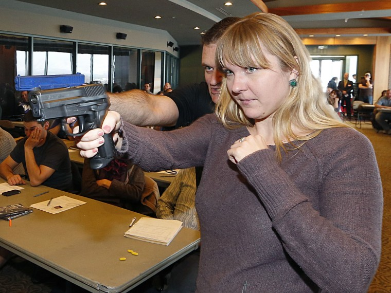 Joanna Baginska (R), a fourth grade teacher at Odyssey Charter School in American Fork, Utah is shown how to handle a 40 cal. Sig Sauer by firearm instructor Clark Aposhian at a concealed-weapons training class to 200 Utah teachers on December 27, 2012...