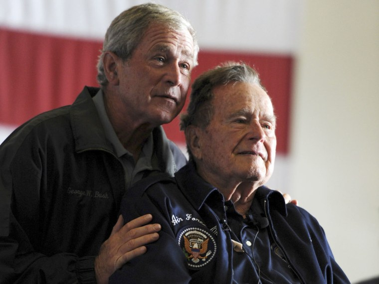 Former Presidents George W. Bush, (L) and George H.W. Bush deliver remarks to the crew during a ceremony aboard the aircraft carrier USS George H.W. Bush (CVN 77) during a promotion and reenlistment ceremony in the Atlantic Ocean in this handout photo...