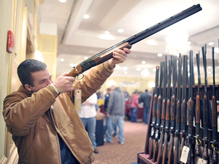 Collin McCarthy of Monroe, Connecticut, looks at a shotgun during the 8th Annual East Coast Fine Arms Show in Stamford, Connecticut January 6, 2013.  (Photo by Timothy A. Clary/AFP/Getty Images)