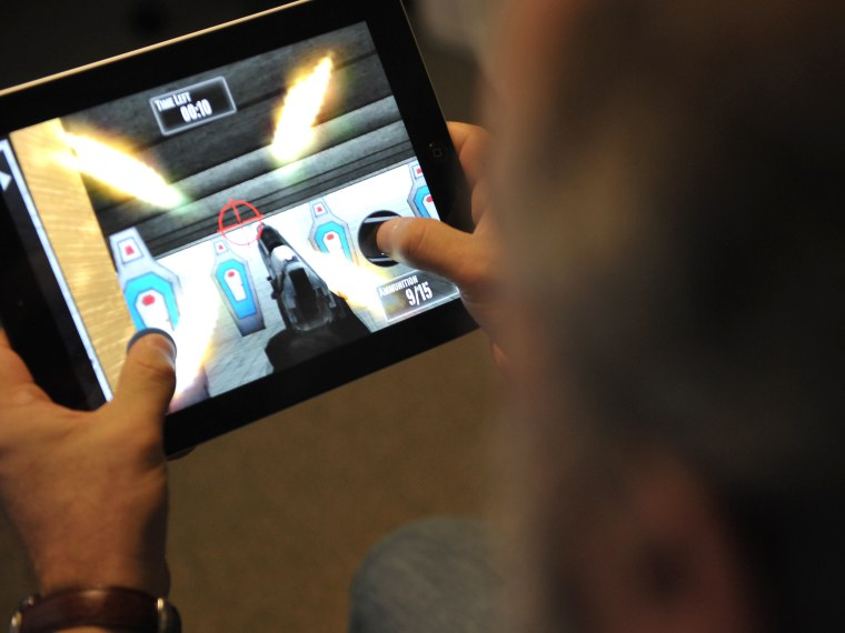 "This January 15, 2013 photo taken in Washington, DC, shows a man playing the newly released National Rifle Association (NRA) iPhone/iPad app, ""NRA: Practice Range."" The new app was released January 14, by the nation's largest gun-industry lobby. The..."