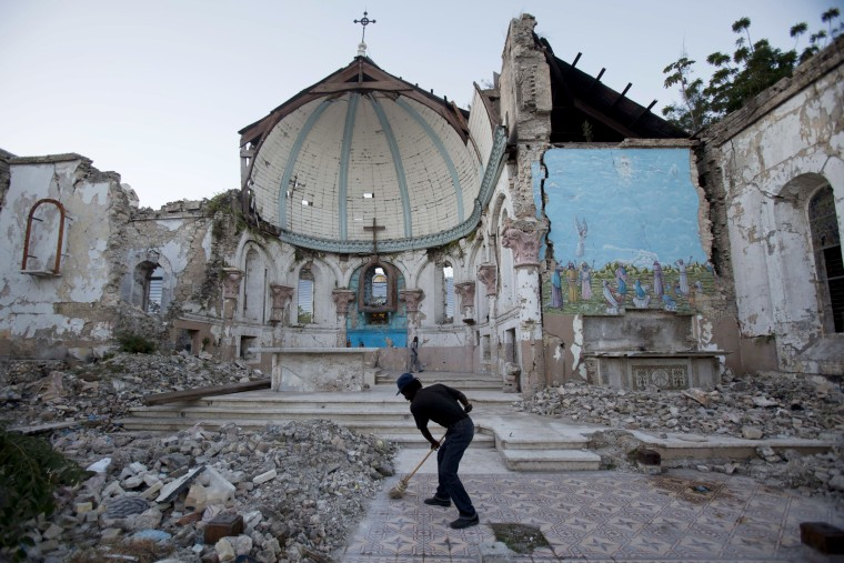 A man sweeps an exposed tiled area of the earthquake-damaged Santa Ana Catholic church, where he now lives, in Port-au-Prince, Haiti, Saturday, Jan. 12, 2013. Haitians recalled Saturday the tens of thousands of people who lost their lives in a...