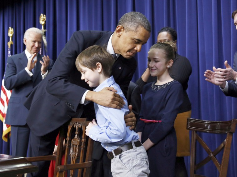 President  Obama hugs a young boy named Grant Fritz -- one of a group of children who wrote the president letters about guns and gun control -- after signing executive orders  on a series of proposals to counter gun violence during an event at the ...