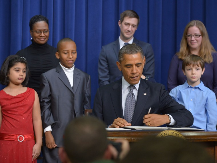 As guests look on, President Barack Obama signs executive actions to curb gun violence at the South Court Auditorium of the Eisenhower Executive Office Building, next to the White House in Washington on January 16, 2013. (Photo by Mandel Ngan/AFP/Getty...