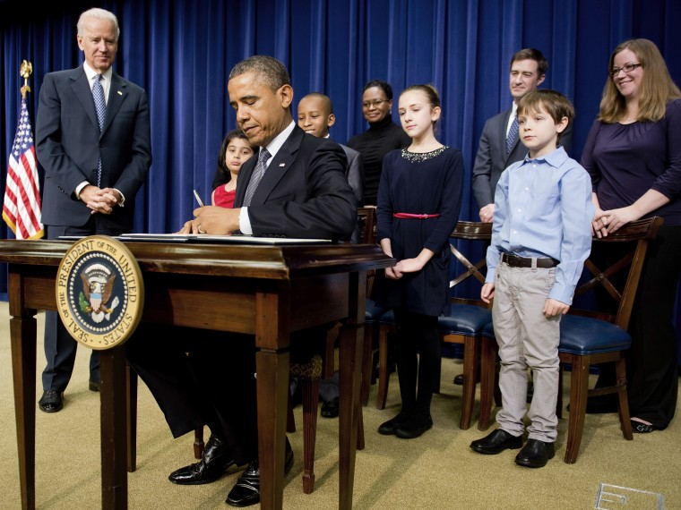 US President Barack Obama (C) signs executive orders with Vice President Joe Biden (L) and invited guests during an event unveiling a package of proposals to reduce gun violence at the White House in Washington, DC, January 16, 2013. Obama signed 23...