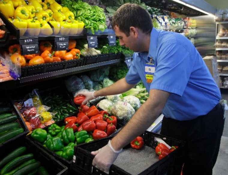 A worker stocks a new Walmart Express store in Chicago July 26, 2011. Chicago low-wage workers such as this one can look forward to additional protections against wage theft under a new city ordinance.(Photo by John Gres/REUTERS)