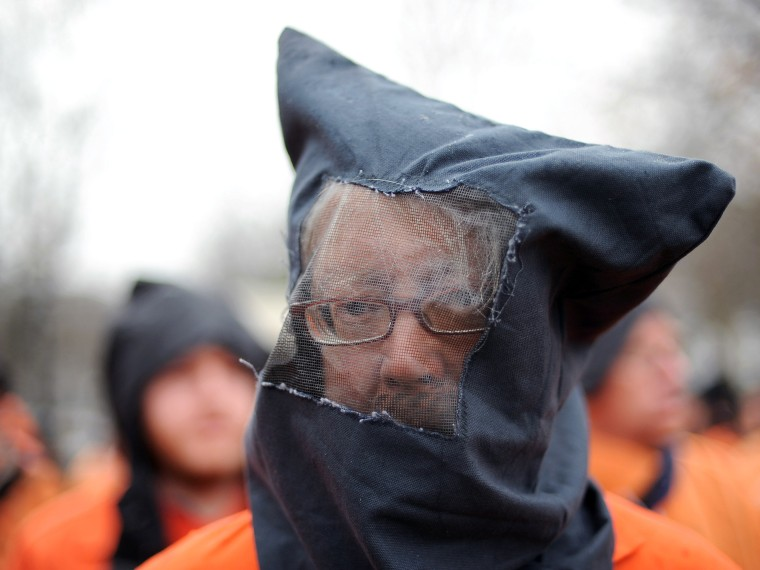 File Photo: David Barrows and fellow members of the organization Witness Against Torture wear orange prison jump suits with handcuffs and a hood over their heads during a demonstration urging the government to close down the detention facility at...