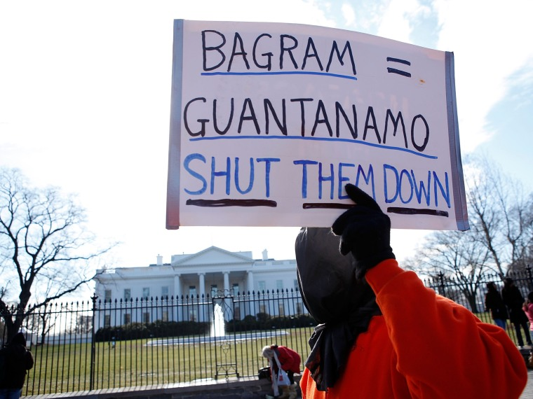 File Photo: A member of Witness Against Torture holds a sign as he protests in front of the White House to mark the eighth anniversary of the opening of Guantanamo Bay detention camp January 11, 2010 in Washington, DC. Protesters called on the Obama...