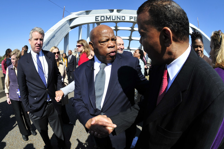 """U.S. Rep. John Lewis, D-Ga., center, is greeted by a well wisher as he pauses for a photo opportunity with members of the the Kennedy family prior to commemorating the 47th anniversary of the """"Bloody Sunday"""" civil rights march from Selma to Montgomery..."""