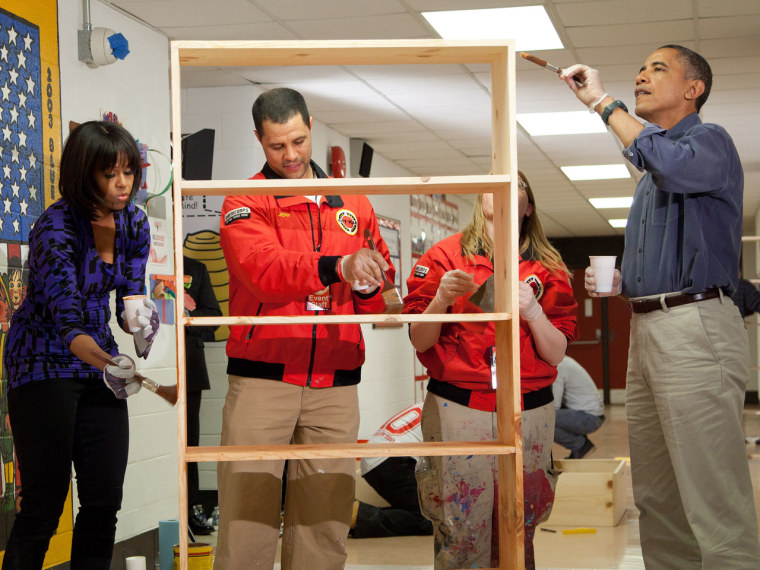 President Barack Obama (R) and first lady Michelle Obama (L) help Jeff Franco (2L), Executive Director of City Year, and Sheri Fisher, a City Year employee, to stain a bookshelf at Burrville Elementary School January 19, 2013 in Washington, DC. The...