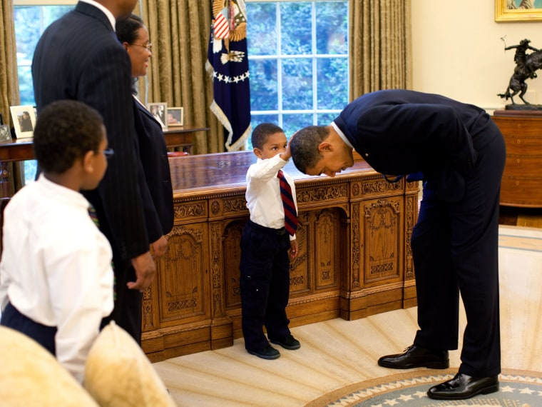 File Photo: In this handout from the The White House, U.S. President Barack Obama bends over so the son of a White House staff member can pat his head during a visit to the Oval Office May 8, 2009 in Washington, DC.  (Photo by Pete Souza/The White...