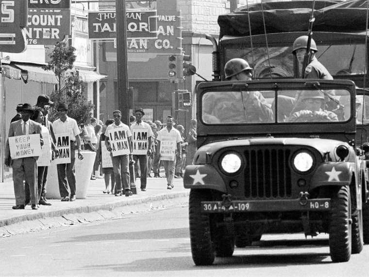 File Photo: Tennessee National Guard troopers in jeeps and trucks escort a protest march by striking Memphis sanitation workers through downtown Memphis Saturday afternoon March 30, 1968. (AP Photo, File)