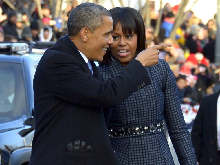 US President Barack Obama and First Lady Michelle Obama walk along Pennsylvania Avenue during the parade following Obama's second inauguration as the 44th US president on January 21, 2013 in Washington, DC. (Photo by Jim Watson/AFP/Getty Images)