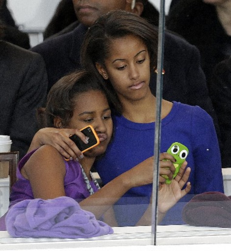 Malia and Sasha Obama look on from the presidential box. (Photo by AP/Gerald Herbert)