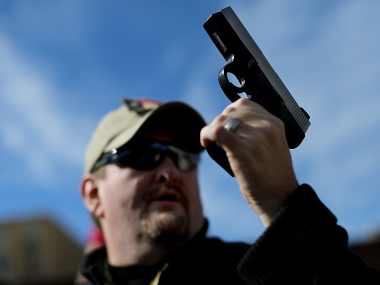 Second Amendment supporter and gun enthusiast Derek Ringley displays an unloaded pistol that was being sold in an impromptu auction across the street from a gun buy back program at the First Presbyterian Church of Dallas on January 19, 2013 in Dallas,...