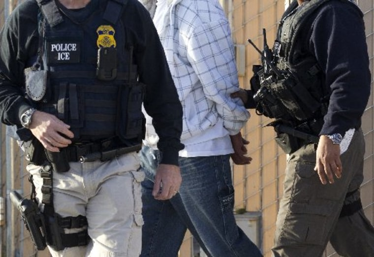 In this March 30, 2012 photo,  Immigration and Customs Enforcement (ICE) agents take a suspect into custody as part of a nationwide immigration sweep in Chula Vista, Calif. (AP Photo/Gregory Bull)
