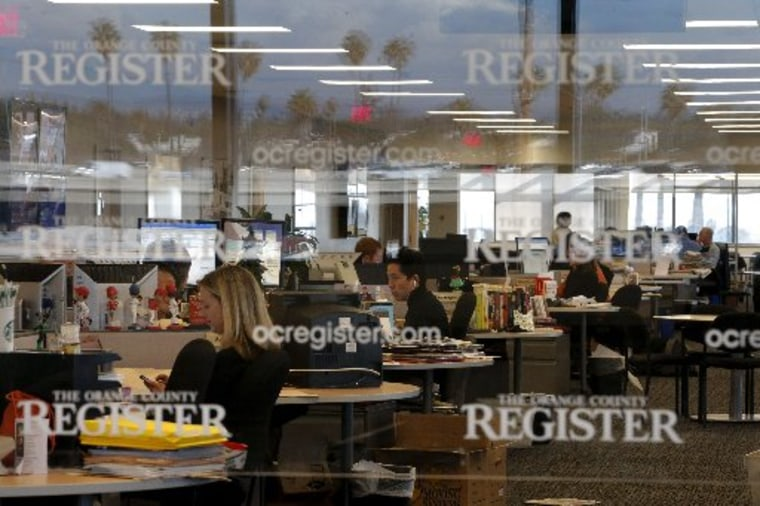 Arts writer Richard Chang, center, works on his computer in the newsroom of the Orange County Register in Santa Ana, Calif., Thursday, Dec. 27, 2012. After years of demoralizing layoffs, one newspaper is trying something novel: hiring more reporters. ...