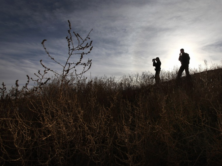 File Photo: U.S. Border Patrol agents Richard Funke and Colleen Agle look for illegal immigrants crossing the U.S.- Mexico border on December 7, 2010 near Nogales, Arizona. Although a new fence has been built along the majority of Arizona's border with...