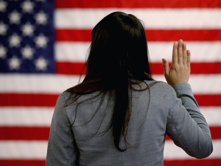 An woman takes the oath of allegiance during a naturalization ceremony at the at district office of the U.S. Citizenship and Immigration Services (USCIS) on January 28, 2013 in Newark, New Jersey. Some 38,000 immigrants became U.S. citizens at the...