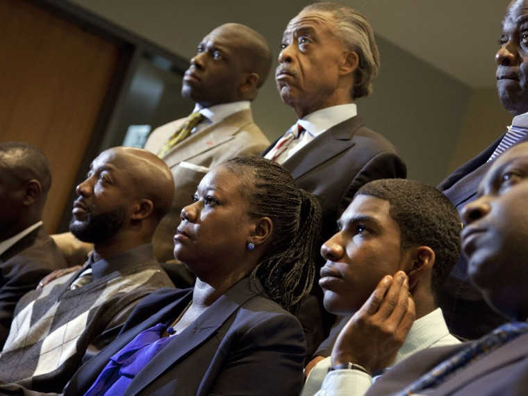 File Photo: Parents of Trayvon Martin who was fatally shot by neighborhood watch captain George Zimmerman in Florida, mother Sybrina Fulton (C), Tracy Martin (Center L) hold hands as they watch a news conference from Washington, with special prosecutor...
