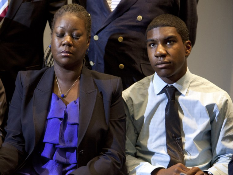 File Photo: The mother of Trayvon Martin, Sybrina Fulton (C) closes her eyes as she and  Trayvon's brother Jahvaris Fulton (R) watch a news conference on Wednesday, April 11, 2012, in Washington, DC as special prosecutor Angela Corey in Sanford,...