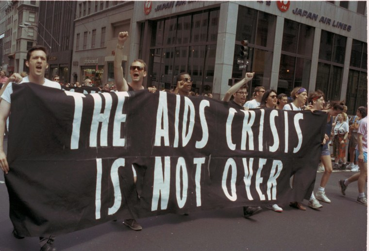 """Marchers during the 21st annual Gay Pride Parade hold a banner that reads """"The AIDS crisis is not over,"""" June 25, 1990.  (AP Photo/Joseph F. Major)"""