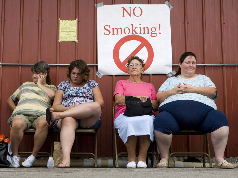 File Photo: Women wait for various medical procedures outside a barn during the  Remote Area Medical (RAM) clinic July 20, 2007 at the Wise County Fairground in Wise, Virginia. Rural families, most with little or no insurance, lined up for hours to...