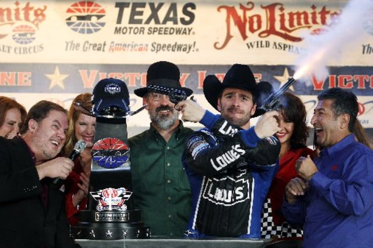 Track President Eddie Gossage, left, ducks as Jimmie Johnson fires blanks out of a revolver while celebrating in victory lane following his win in the NASCAR Sprint Cup Series auto race at Texas Motor Speedway, Sunday, Nov. 4, 2012, in Fort Worth,...