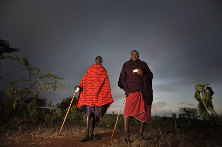 Two Masaai walk with their ID card on their hands to reach a polling station to vote in a general election in Kumpa, Kenya, Monday March 4, 2013. Five years after more than 1,000 people were killed in election-related violence, Kenyans went to the...