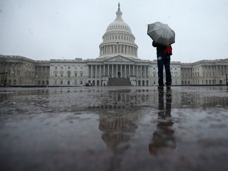 A tourist takes cover underneath an umbrella while snapping a photo of the U.S. Capitol as snow and rain falls March 6, 2013 in Washington, DC. A late winter storm is expected to cover the Mid-Atlantic region after dropping almost a foot of snow across...