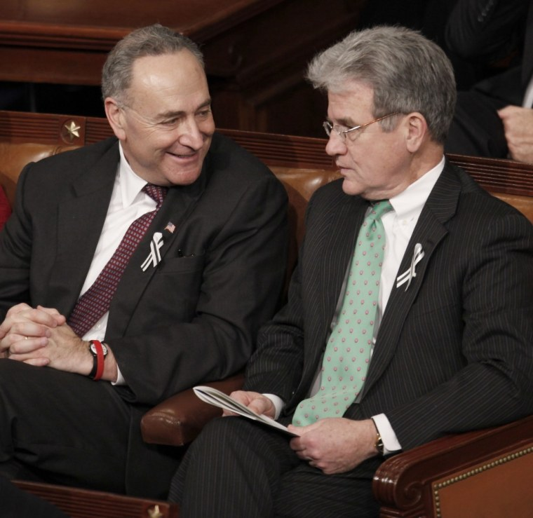 FILE - In this Jan. 25, 2011 file photo, Sen, Charles Schumer, D-N.Y., left, talks with Sen. Tom Coburn, R-Okla., on Capitol Hill in Washington, during President Barack Obama's State of the Union address (AP Photo/Evan Vucci, File)