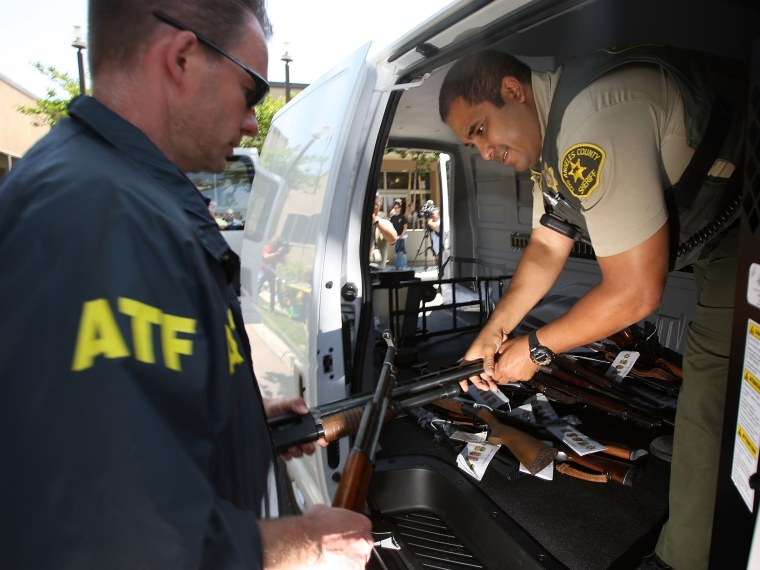 File Photo: Officers load some of about 125 weapons confiscated during what the federal authorities say is the largest gang takedown in U.S. history into a van after a press conference to announce the arrests of scores of alleged gang members and...