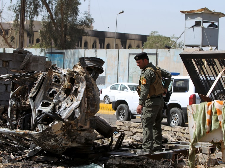 A member of Iraq's internal security forces inspects the damage outside the Iraqi justice ministry in Baghdad on March 15, 2013, a day after militants staged an apparently unsuccessful assault. A coordinated string of bombings and a brazen assault on...
