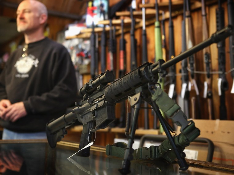 File Photo: An AR-15 style rifle sits on the counter by Craig Marshall as he assists a customer at Freddie Bear Sports sporting goods store on December 17, 2012 in Tinley Park, Illinois.  Americans purchased a record number of guns in 2012 and gun...