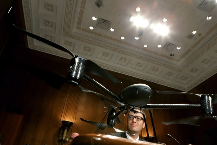 Mesa County Sheriff's Office Unmanned Aircraft Program Manager Benjamin Miller testifies before the Senate Judiciary Committee while framed by a Draganflyer X6 remote-controlled  miniature helicopter in the Dirksen Senate Office Building on Capitol...