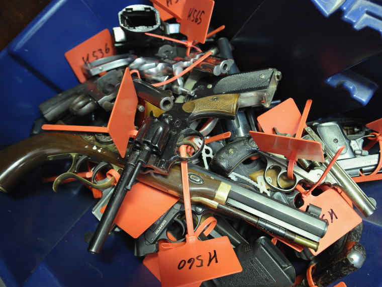Tagged handguns lay in a bucket during a gun buyback program on March 9, 2013 in Keansburg, New Jersey.  (Photo by Michael Loccisano/Getty Images)