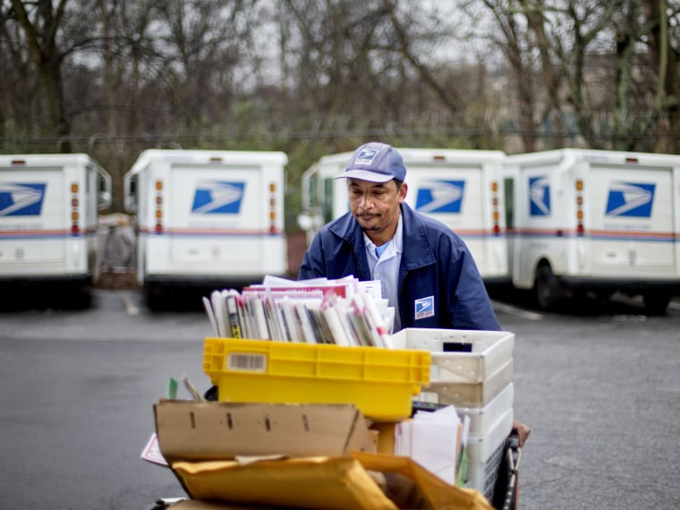 U.S. Postal Service letter carrier of 19 years, Michael McDonald, gathers mail to load into his truck before making his delivery run in the East Atlanta neighborhood, Thursday, Feb. 7, 2013, in Atlanta. The financially struggling U.S. Postal Service...