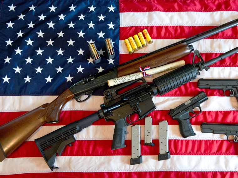 This February 4, 2013 photo illustration in Manassas, Virginia, shows a Remington 20-gauge semi-automatic shotgun, a Colt AR-15 semi-automatic rifle, a Colt .45 semi-auto handgun, a Walther PK380 semi-auto handgun and various ammunition clips with a...