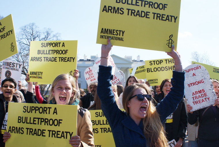 Amnesty International protestors demonstrate outside of the White House in Washington, DC, on March 22, 2013.  The protestors were urging President Obama to support a bulletproof Arms Trade Treaty. Photo by Nicole Sakin/AFP/Getty Images)