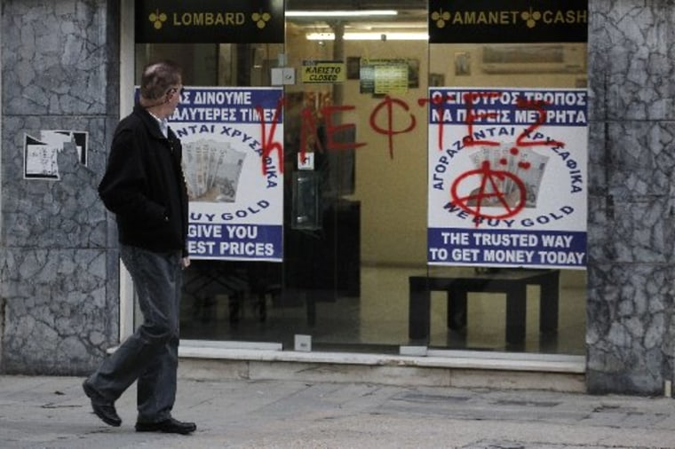 "A man passes a sprayed entrance of a store that buys gold which reads in Greek ""thieves"" in capital Nicosia, Cyprus, Monday, March 25, 2013. (AP Photo/Petros Giannakouris)"