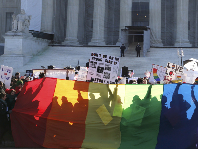 Anti-Proposition 8 protesters are shadowed by a rainbow banner in front of the U.S. Supreme Court in Washington, March 26, 2013. (Photo by Jonathan Ernst/Reuters)
