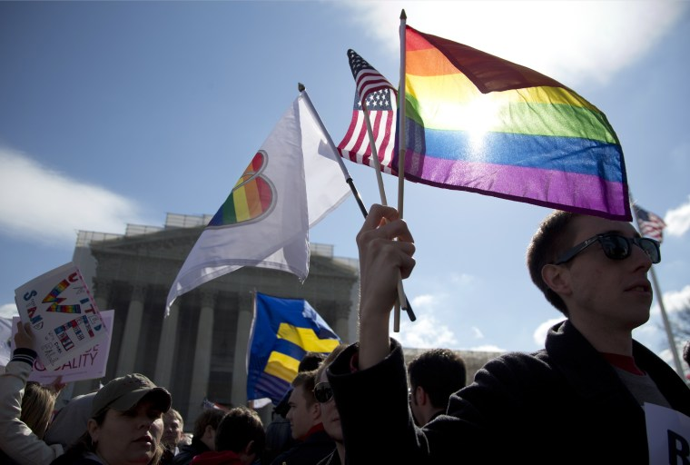 Kevin Coyne of Washington holds flags in front of the Supreme Court in Washington. (Photo by Carolyn Kaster/AP)