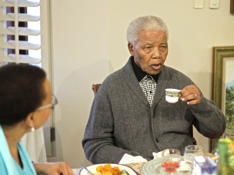 File Photo: Former South African President Nelson Mandela has tea with his wife Graça Machel, left, as he celebrates his birthday with family in Qunu, South Africa, Wednesday, July 18, 2012.  (Photo by Schalk van Zuydam/AP Photo, File)