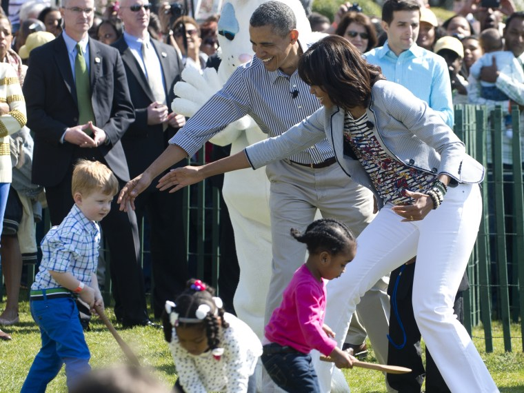 President Barack Obama  and Michelle Obama (R) cheer on children as they race to roll eggs as they participate in the White House Easter Egg Roll April 1, 2013. (Photo by Saul Loeb/AFP/Getty Images)