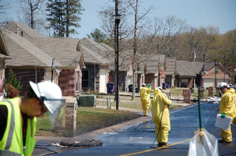 Crews work to clean up oil in Mayflower, Ark., on Monday, April 1, 2013, days after a pipeline ruptured and spewed oil over lawns and roadways. (AP Photo/Jeannie Nuss)